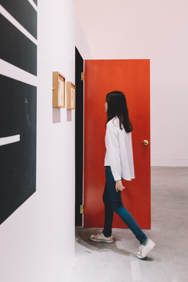 A girl entering red door