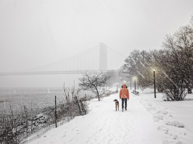 Man is walking with a dog in snow next to Hudson River New York City, NY, USA