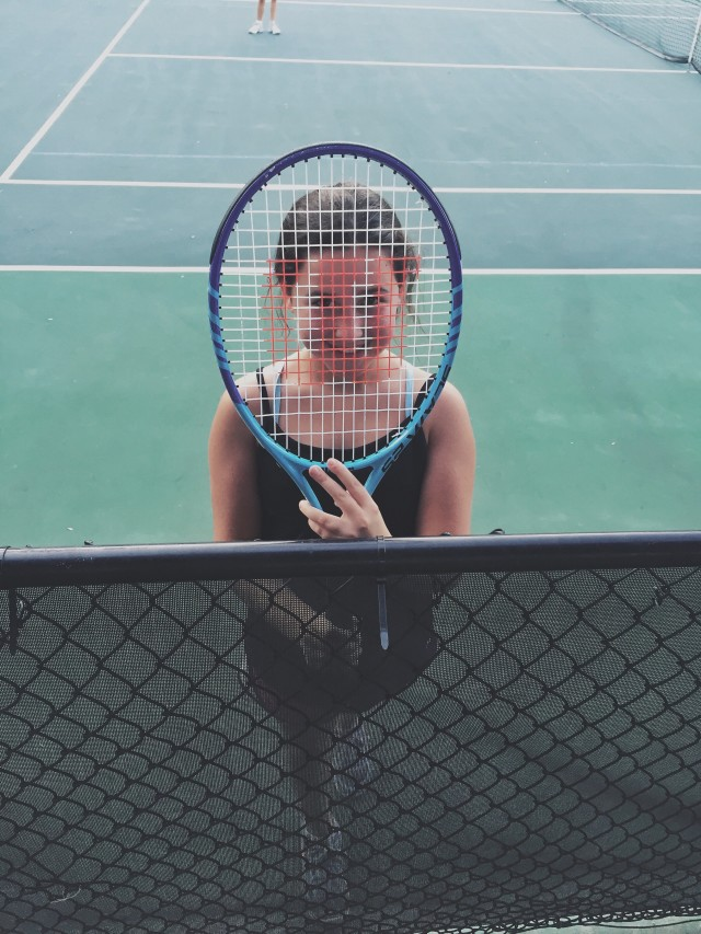 Smile behind a tennis racket