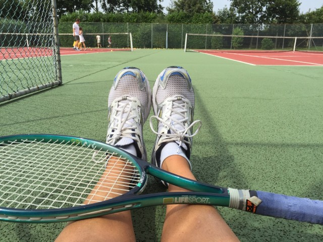 Tired sitting on a tenniscourt