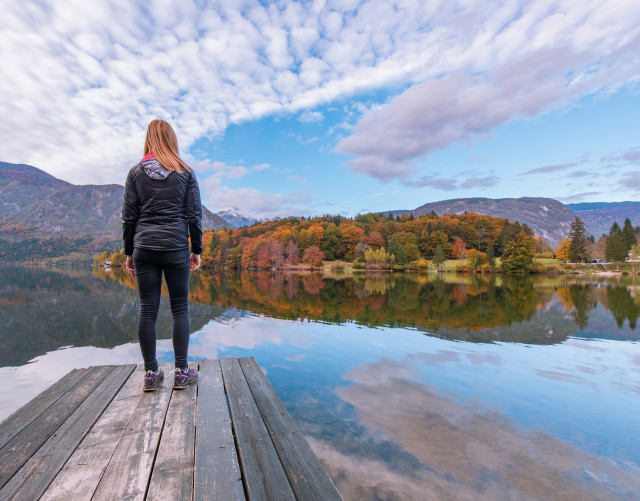 Female hiker standing on a pier at lake Bohinj in Julian Alps mountain range.