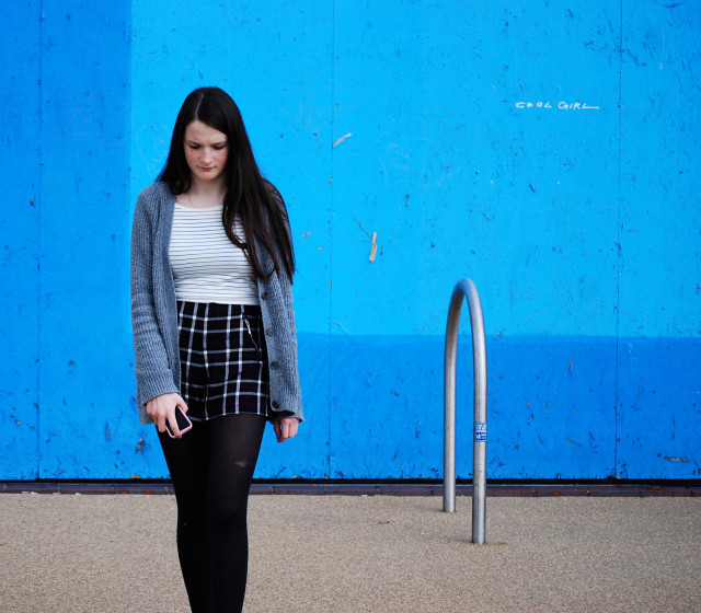 Teenage girl walking in front of monochromatic background