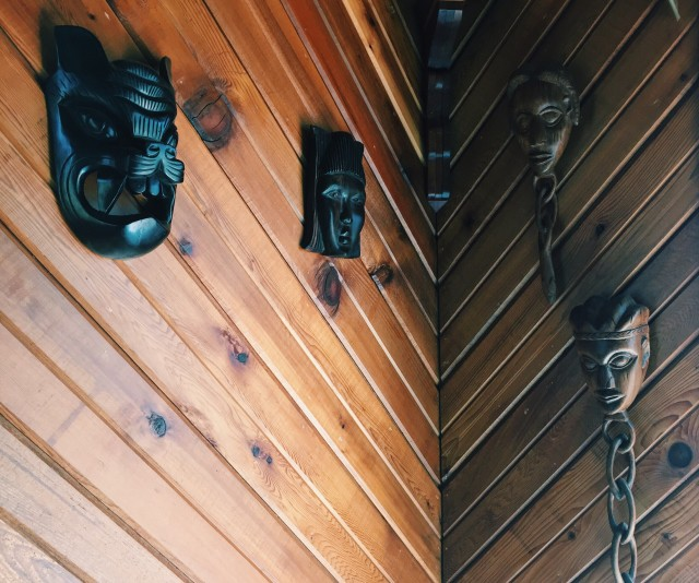 Cultural wooden facial artifacts hanging on an angled wooden wall
