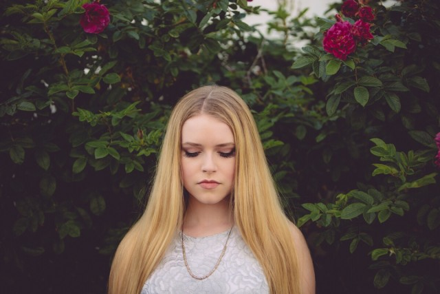 Girl with long blonde hair looking down