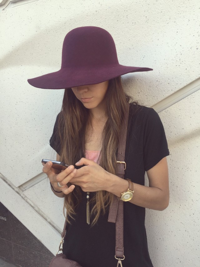A young lady wearing a purple hat is leaning against The Broad Museum while looking down at her iPhone.