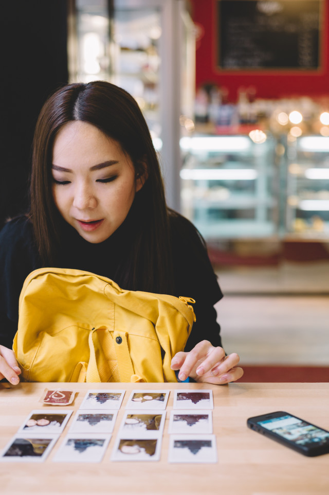 Woman arranging polaroid photos on wooden table