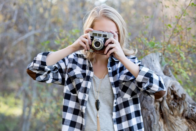 GIRL IN PLAID TAKING A PICTURE