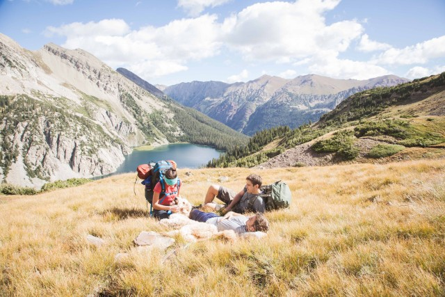 Hikers relax on a mountainside meadow in Colorado.