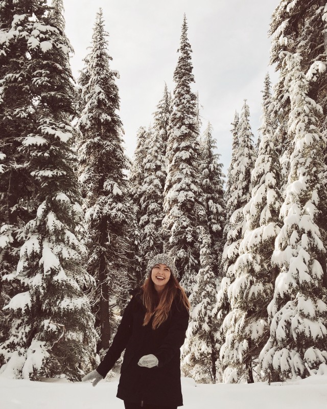 Woman enjoys a winter hike in the woods.
