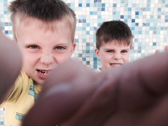 Kids grabbing the camera against tile wall.