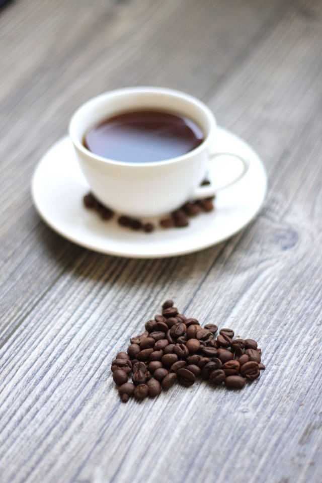 White cup of coffee and coffee beans in the shape of heart