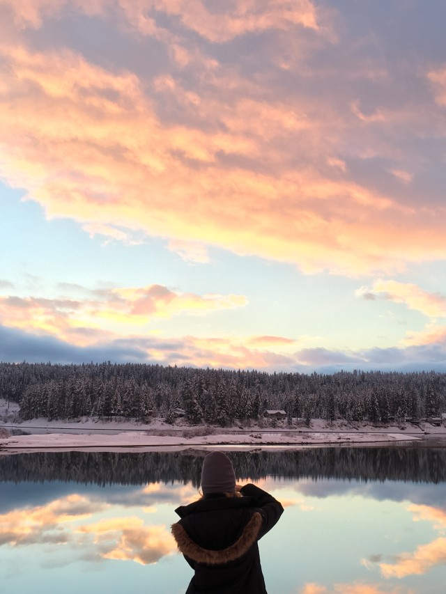 Young photographer at a glassy winter River at sunset