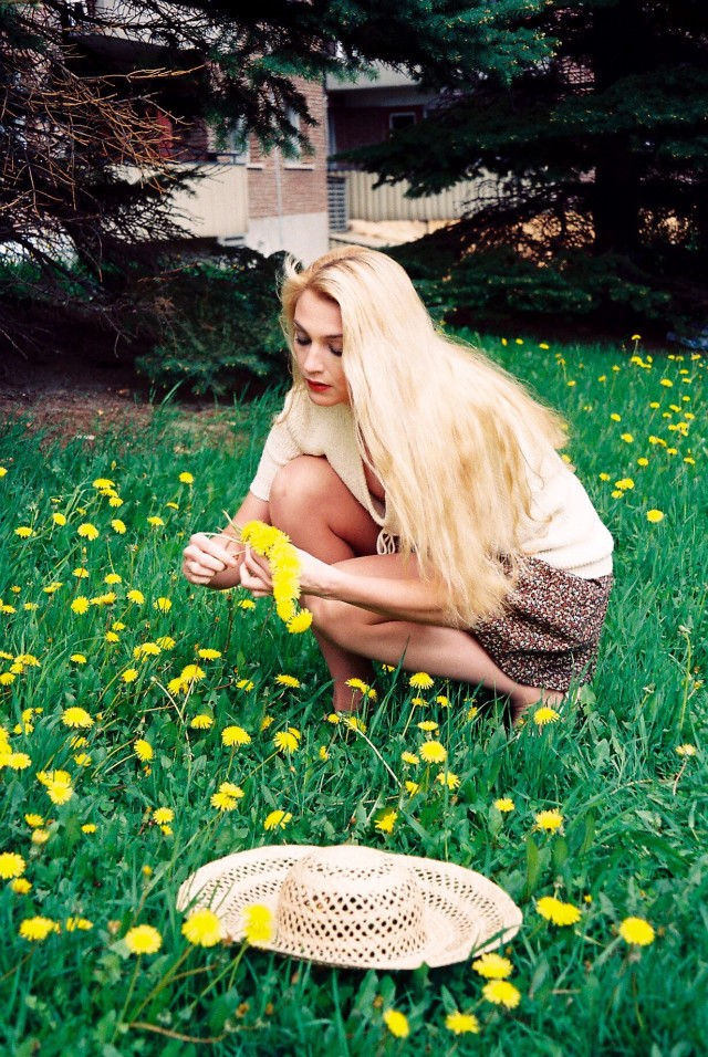 Young woman picking dandelions