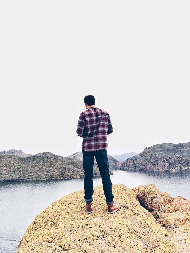 Young man standing on a cliff overlooking a lake.