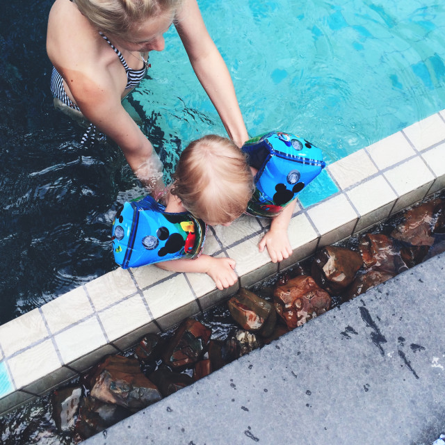 Mother teaching child to swim