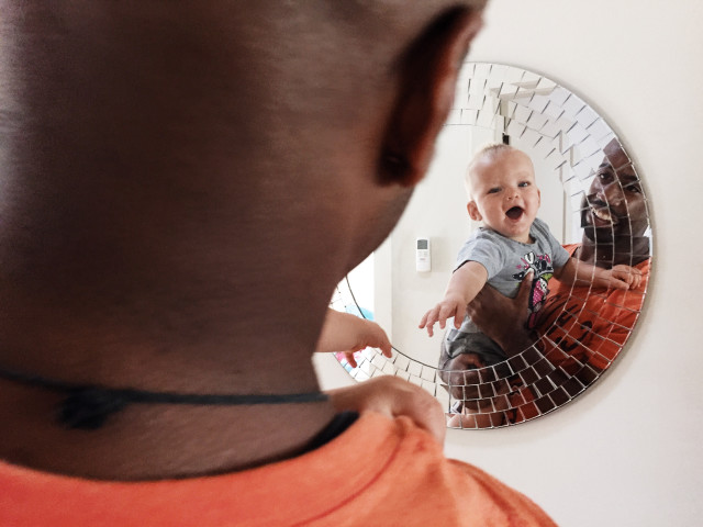 Dad holding son and looking at the mirror