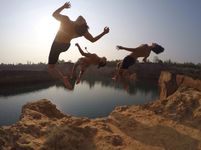 Three athletic men back flipping off a cliff
