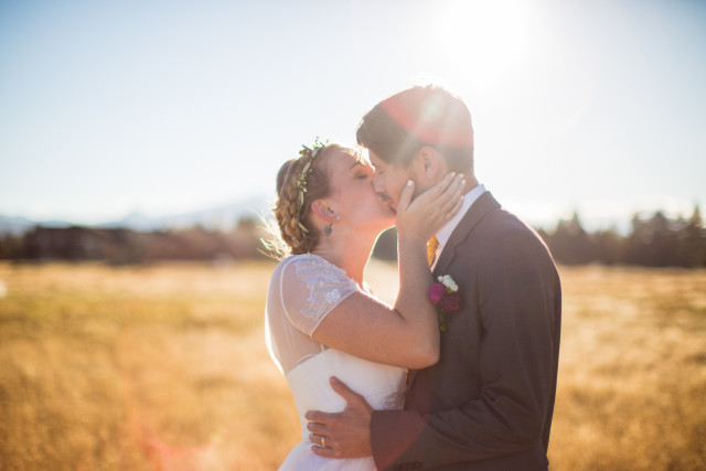 Woman, wearing a wedding dress kisses a man, wearing a gray suit in the middle of a field in front of a mountain at sunset.