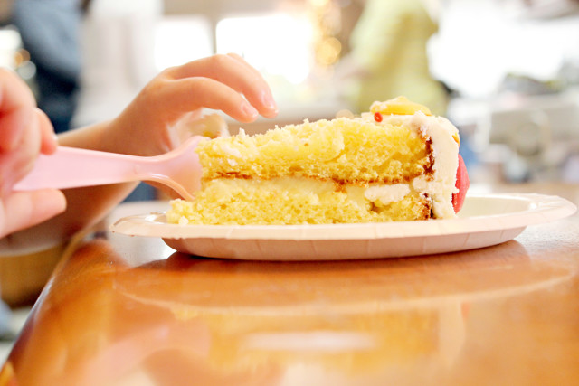 Macro of little girl eating delicious layered birthday cake