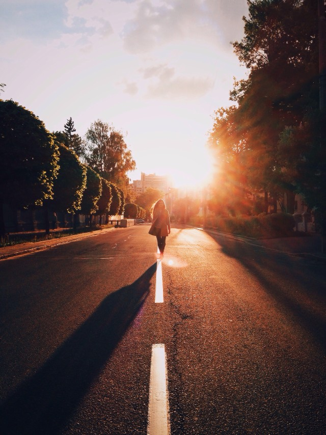 Woman walking on the sunny road