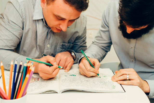 Men coloring relaxation books at work. Creativity at work, office break