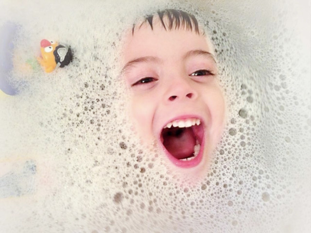 Young child in the bath with bubbles and a bath toy.