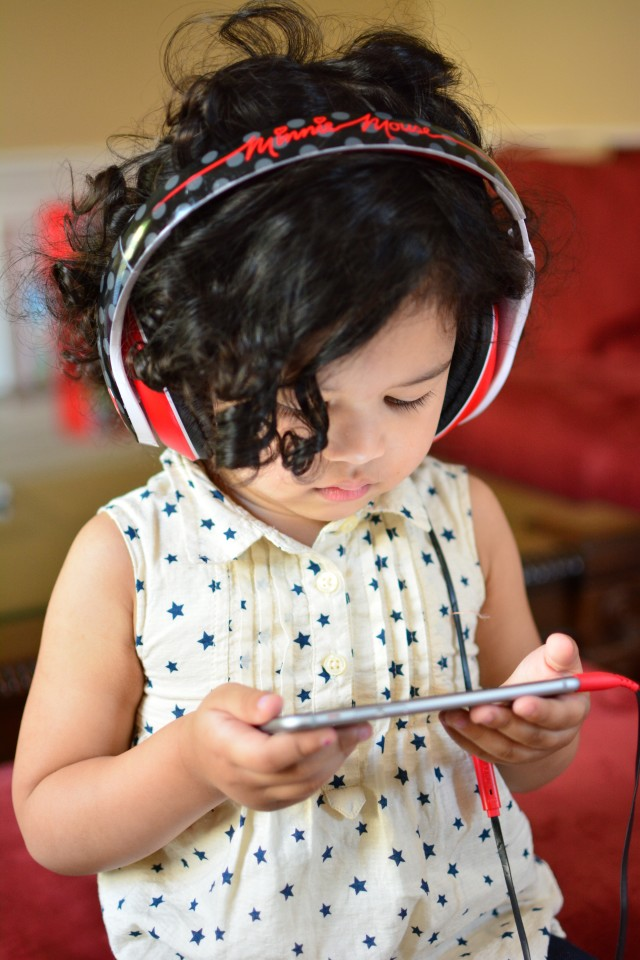 Toddler using mobile phone and headphones