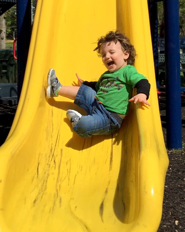 A happy kid sliding down the sliding board