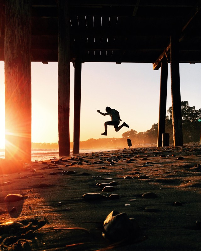 Teenager jumping under pier at sunset.