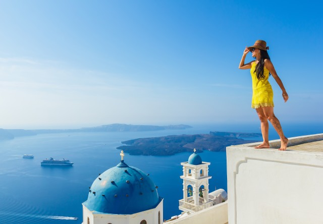 Female tourist enjoys breathe taking view of Santorini