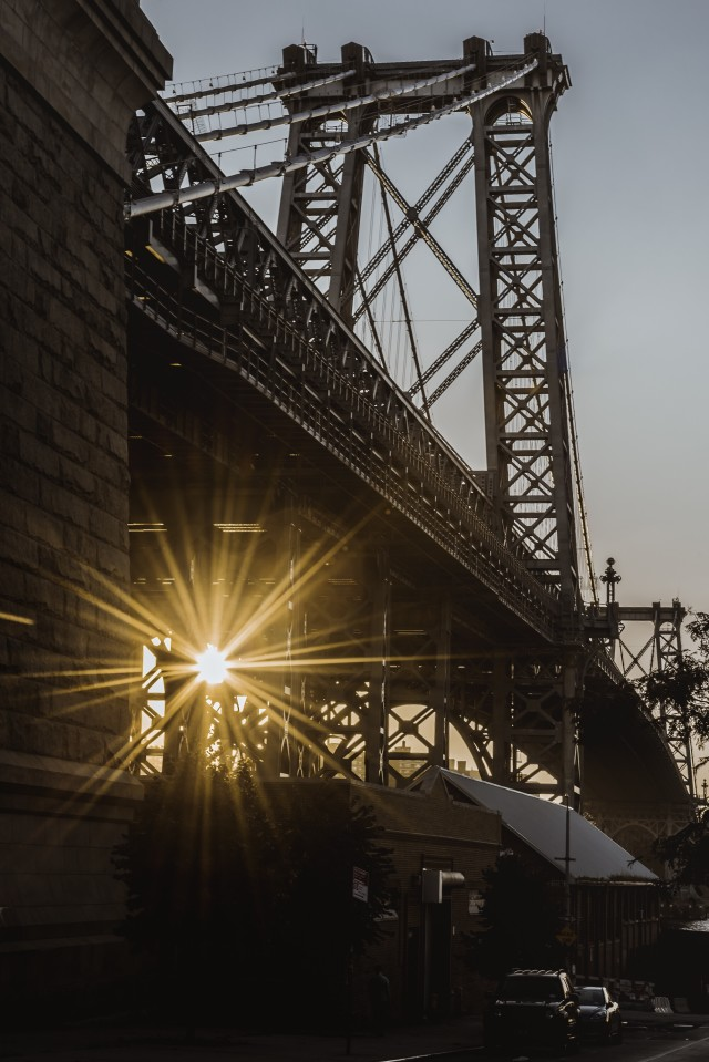 The setting sun peeking through underneath the Williamsburg Bridge.