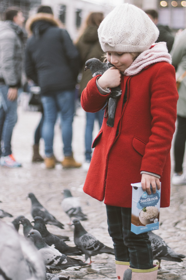 Girl standing in the middle of Dam square in Amsterdam hugging a pigeon