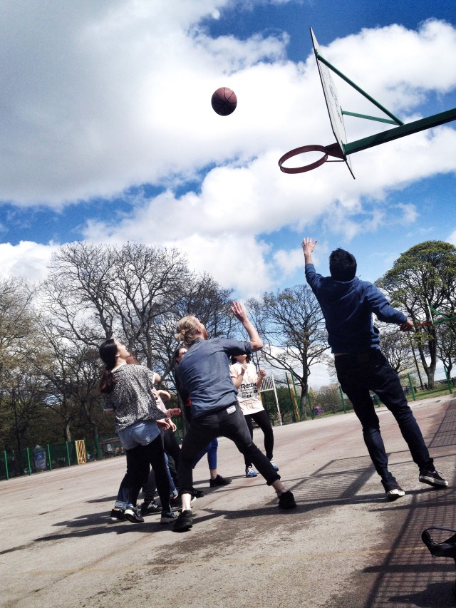 Friends supporting each other in a basketball game inside a sunny park.