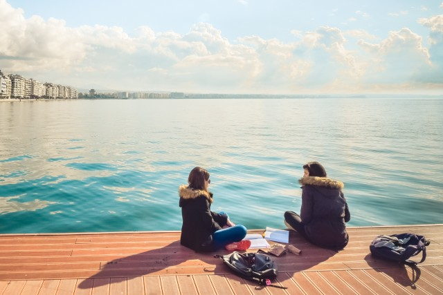 Two Friends Teenager Student Girls Reading Their Books And Talking Outdoor In Front Of The Sea At Port Dock