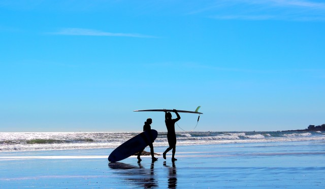 Man and woman's silhouette on blue background beach with surf boards getting ready to go surfing.
