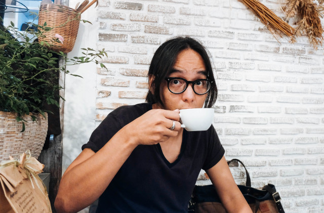 A man sipping a cup of coffee at the cafe