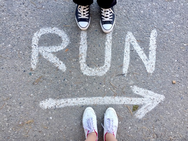 Top view of man's feet wearing black and white sneakers and woman's feet wearing white and pink sneakers standing near run sign