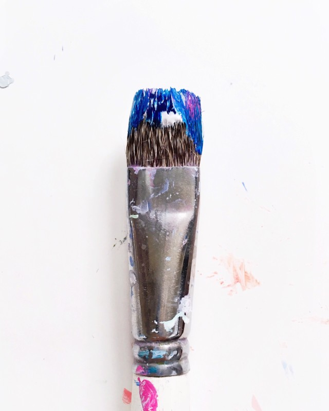 Close up detail of single paintbrush with wet blue paint in bristles over a stained white background.