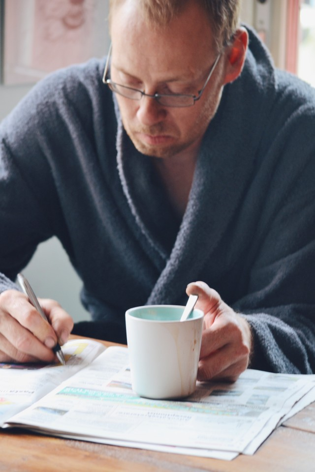 Man doing crosswords and drinking coffee in the morning