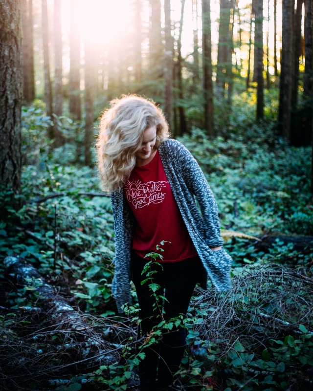Young woman exploring in the evergreen forest at golden hour