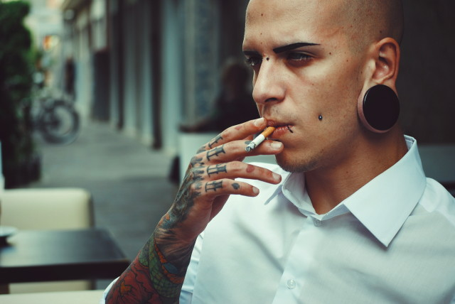 Alternative tattoed boy model with cigarette and white formal shirt. Bokeh background.