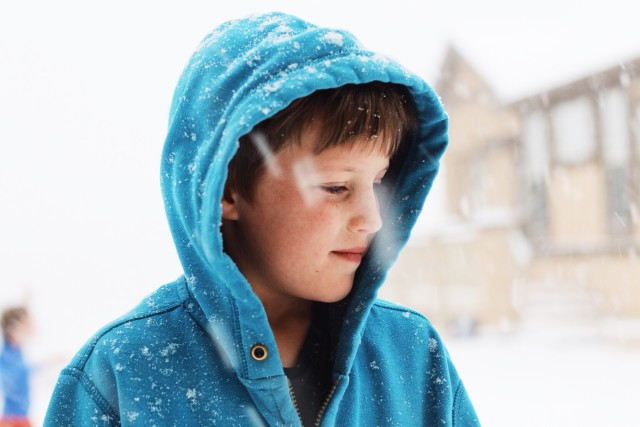 Little brother playing in the snow