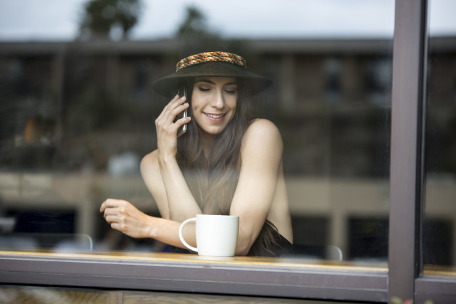 Image of a happy beautiful attractive woman having an intimate conversation while talking on her smartphone in a coffee shop, seen through glass reflection window (model released).