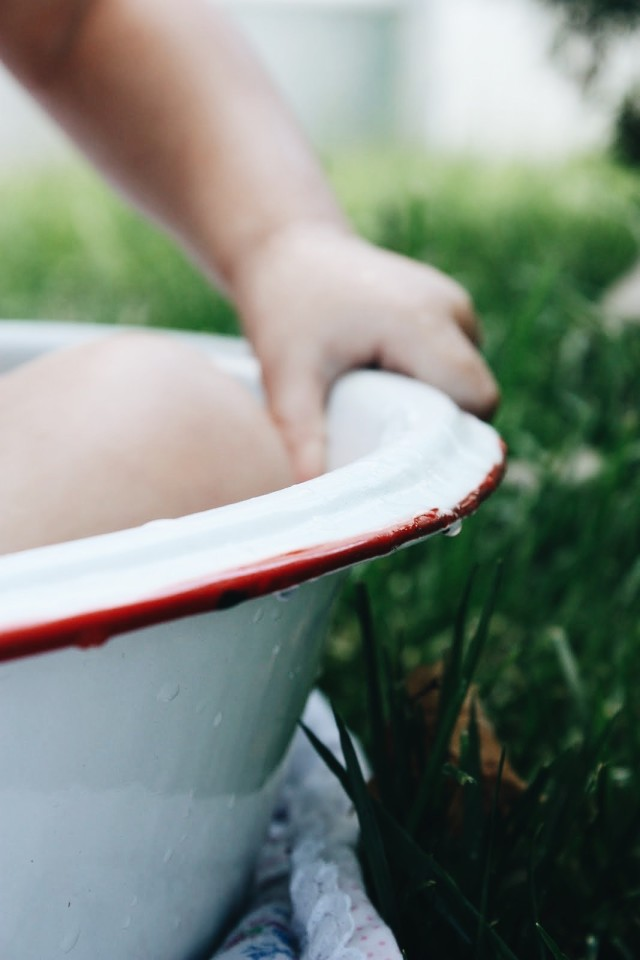 Baby/Toddler gripping a vintage wash basin.