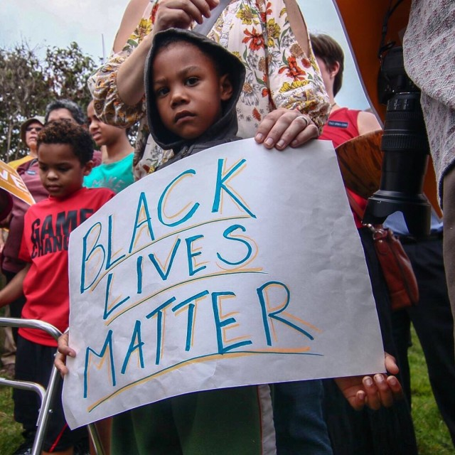 "A little boy holds a sign that reads ""Black Lives Matter"" during a community support rally."