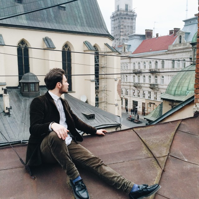 man in vintage clothing sitting on the roof