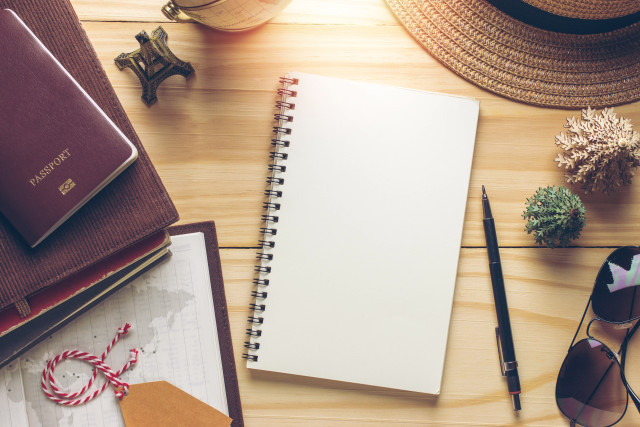 Notebook and travel objects on grunge wooden background with vintage filter