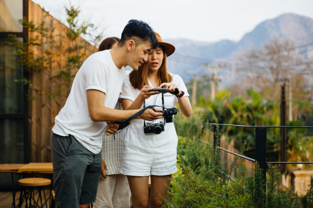 man and woman taking photos with camera and mobile