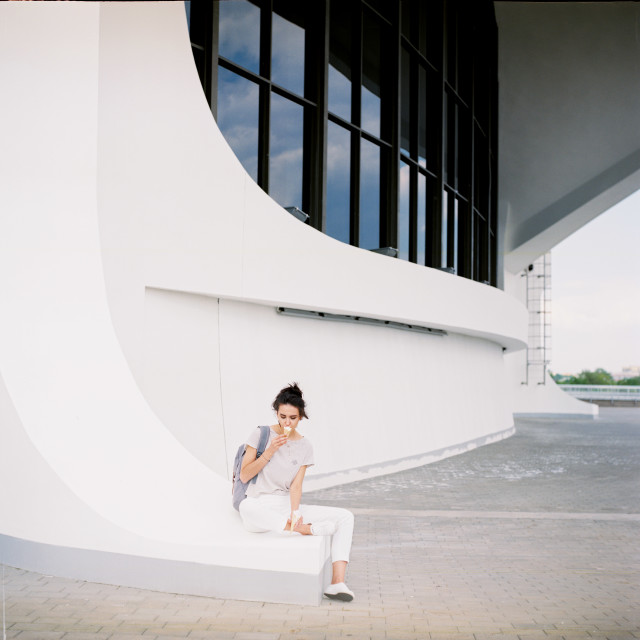 Girl sits and eats ice-cream. Film photo 120mm