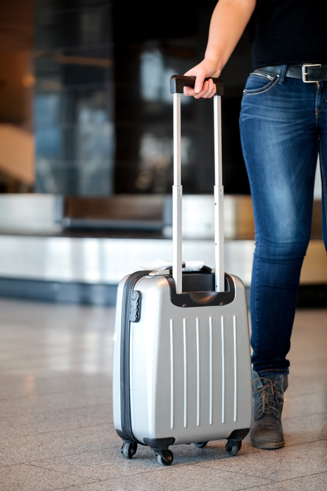 Collecting luggage at the airport terminal when traveling with a person in jeans and boots holding the extended handle on a suitcase, with copyspace